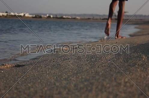 Long shot for Red sea shore and male feet walking passing by, at Wadi Lahmi at day - 5D