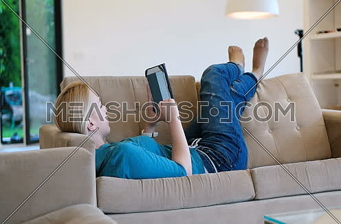 woman using tablet on couch in modern villa home