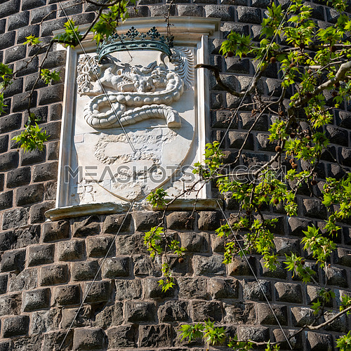 Details of the Sforza Castle (Castello Sforzesco) with the coat of arms of the Visconti noble family with a snake that swallows a human (Biscione). Milan, Italy.