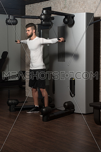 Handsome Man Is Working On His Shoulders With Cable Crossover In A Modern Gym
