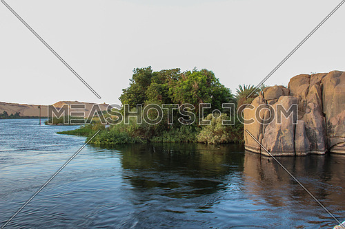 a photo from Aswan city, Egypt showing a view for the river Nile , rocks and landscape