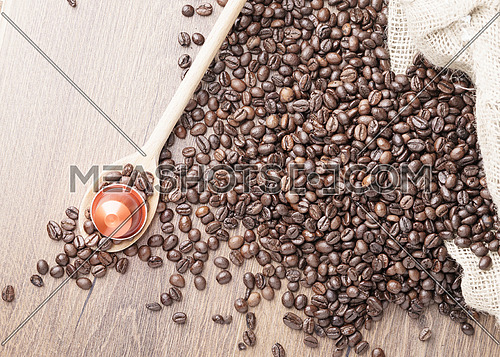 Coffee capsule on wooden spoon and roasted coffee beans with burlap sack on wooden background,top view.