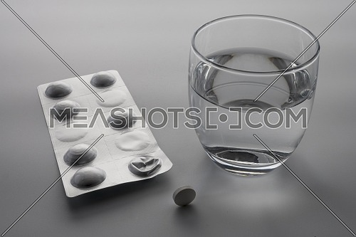 Blister pack of pills next to a glass of water, conceptual image
