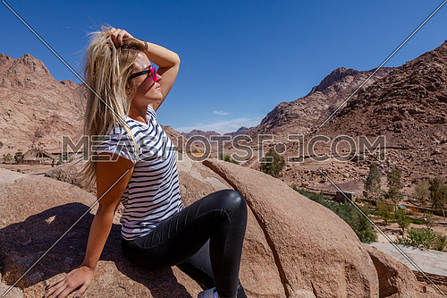 long shot for a female tourist stiing on a rock explore Sinai Mountain for wadi Freij by day.