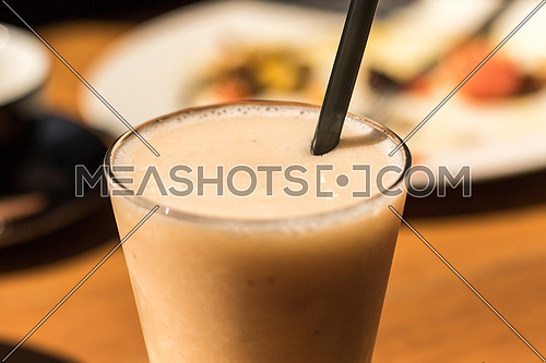 Close up for glass filled with juice and black straw