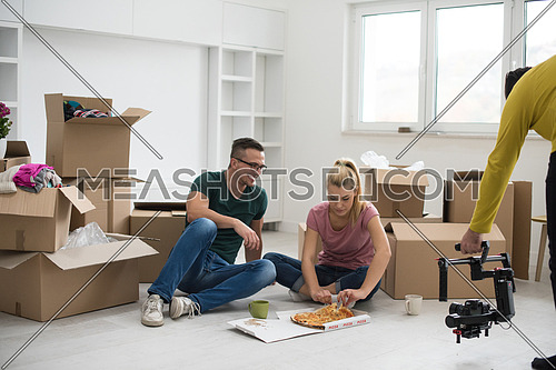 cameraman videographer filming happy young couple have a pizza lunch break on the floor after moving into a new home with boxes around them
