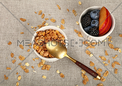 Close up portion of muesli granola breakfast with yogurt, fruits and berries, elevated, high angle view