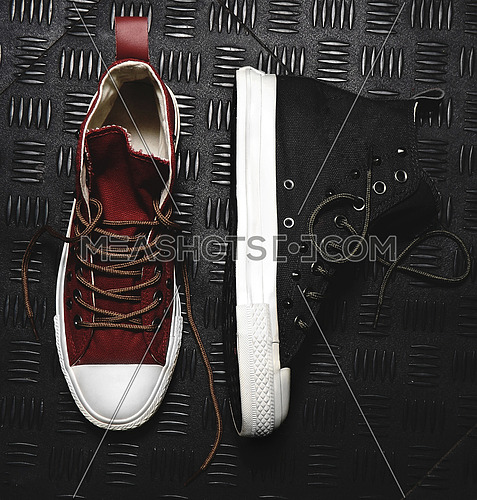 black shoes and red shoes on black metal background