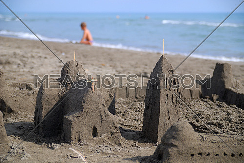 A sand castle in foreground  while a baby playing by the beach