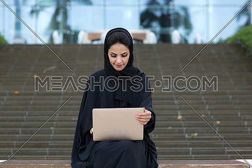 Mid-shot for Saudi lady setting down, working on laptop, wearing black abaya in front of glass building ladder in background at day.