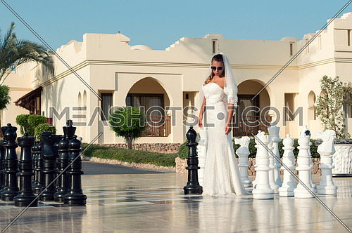 Bride wearing white standing between large scale chess pieces