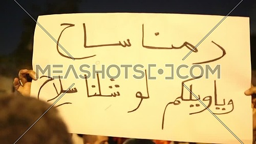 Protesters holding signs at near the presidential palace against Morsi's constitutional declaration at night - December 2012