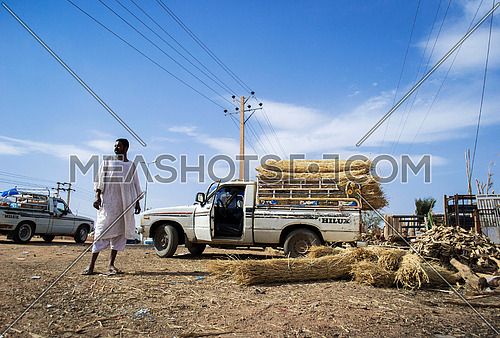A sudanese driver standing beside his pick up ready to transport hay