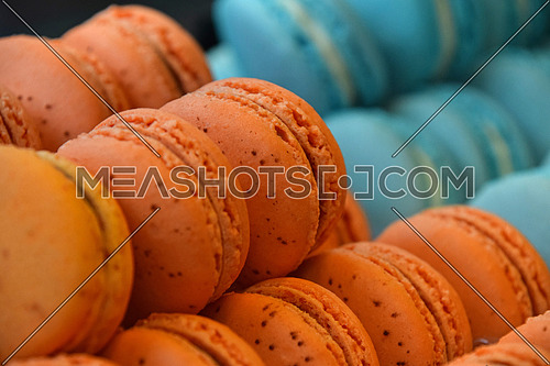 Fresh baked orange and blue macaroon pastry cookies (macarons, macaroni) in retail store display, close up, low angle view