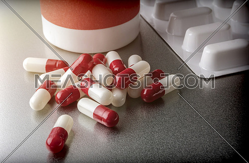 Some capsules red and white next to boats of plastic, conceptual image