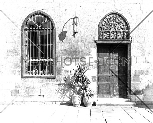 Black and white high contrast shot of old abandoned stone bricks wall with arched wooden door and window covered with wrought iron bars and lantern in a sunny day, Cairo, Egypt