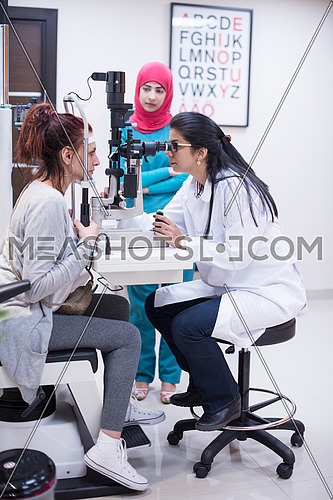 Professional middle eastern oculist is checking human vision with equipment in the modern clinic