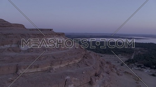 Orbiting around a Photographer at sunrise on top of the mountain in Siwa, Western Desert, Egypt