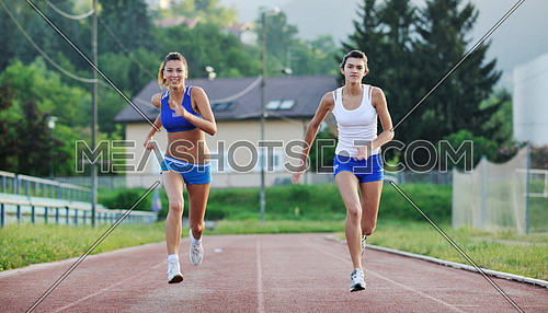 young girl morning run and competition on athletic race track