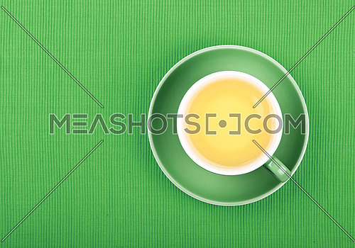 Full cup of clear green tea on saucer over green textile tablecloth, close up, elevated top view