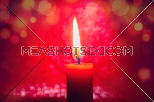 Single burning red candle conceptual of celebration, Christmas or Advent