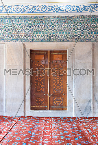 Wooden aged engraved door, marble wall and ceramic tiles with floral blue decorative patterns, Sultan Ahmet Mosque (Blue Mosque), Istanbul, Turkey