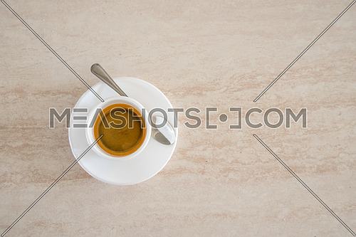 Top view of white cup of coffee with metal spoon,background and copy space.