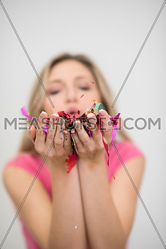beautiful young woman celebrating new year and chrismas party while blowing confetti decorations to camera
