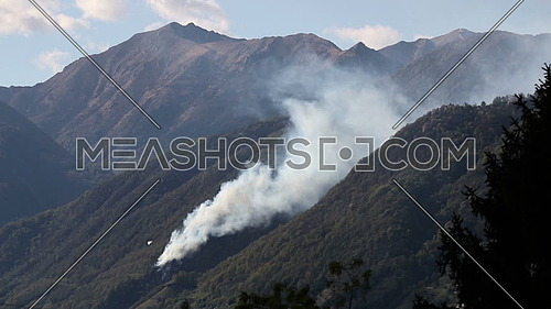 Fire fighting efforts are under way with helicopters to put out forest fires in the mountains