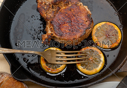 pork chop seared on iron skillet with lemon and spices seasoning