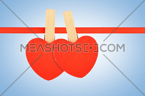 Valentine day template, two red wooden hearts with clothes pins on textile ribbon over sky blue grain noise gradient