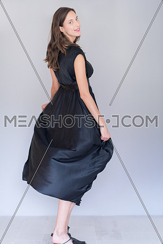 portrait of Beautiful young woman wearing a black dress isolated on white background