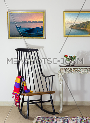 Classic rocking chair and two old books on old style vintage table on background of off white wall with two hanged paintings with clipping path for paintings