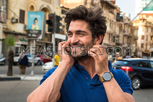 close up young man talking in mobile phone in the street in korba area at day