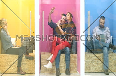 group of people in colorful startup environment having fun and using technology in split rooms