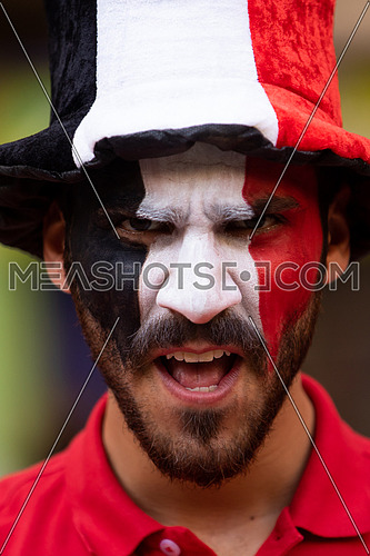 A male Egyptian fan painting a flag on his face wearing supporter's hat