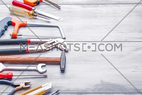 Screwdriver,hammer,tape measure and other tool for construction tools on gray wooden background with copy space,industry engineer tool concept.still-life.