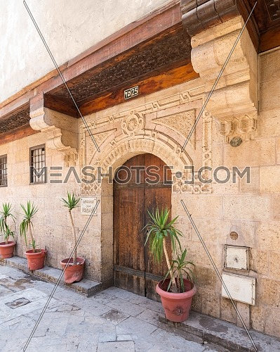 Angled view of old stone bricks decorated wall with arched wooden door, Entrance of old Ottoman historic house of Moustafa Gaafar Al Selehdar, Moez Street, Old Cairo, Egypt