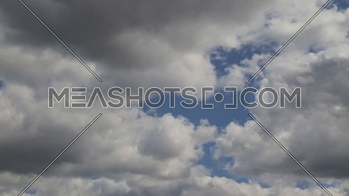 Time lapse clip of white fluffy clouds over blue sky