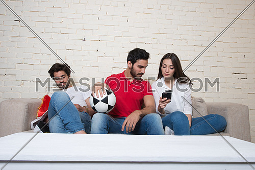 A group of middle eastern  friends watching a football game in the living room