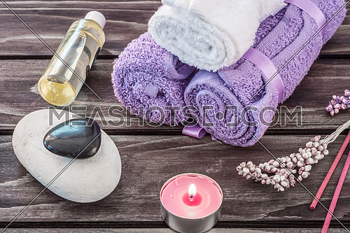 Spa concept. Lavender oil, lavender flowers and bath white and purple towels on wooden background.