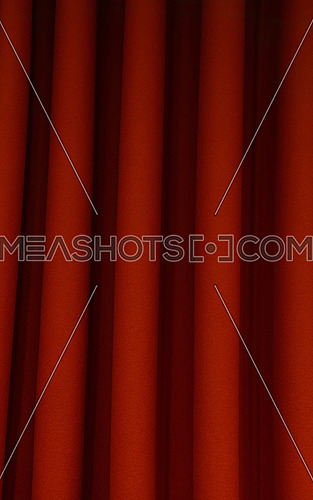 Heavy dark red pleated textile felt curtain background with portiere drape folds, side view close up