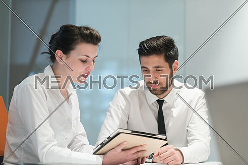 Young couple working together on tablet  computer. Teamwork, help, support concept.  Business group  at modern startup office meeting room interior working online on project plans.