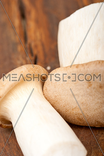 bunch of fresh wild mushrooms on a rustic wood table