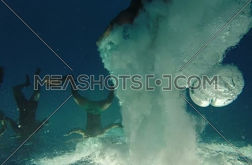 Shot for a male jumping of a boat into the red sea till goes underwater at Red Sea at Day