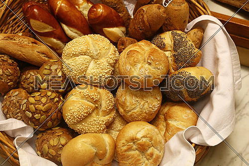Close up several assorted fresh bread buns in basket on retail display of bakery, high angle view