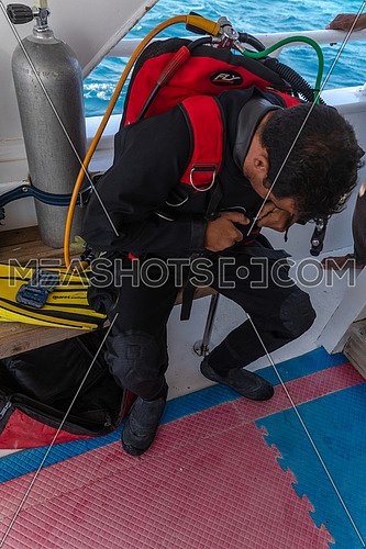 Mid shot for diver getting ready to dive into Red Sea from a yacht by day