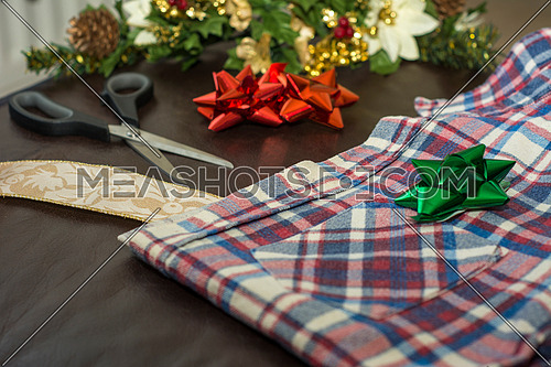Christmas gift wrapping a men's plaid shirt.