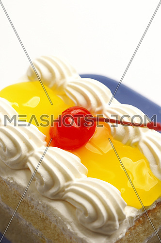 piece of lemon jelly cake with cherry on top on white background