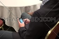 close shot from behind for a business man wearing suit and using his cell phone in a conference.